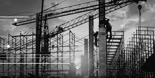 Scene on building site at sunset showing multiple cranes and scaffolding in silhouette.